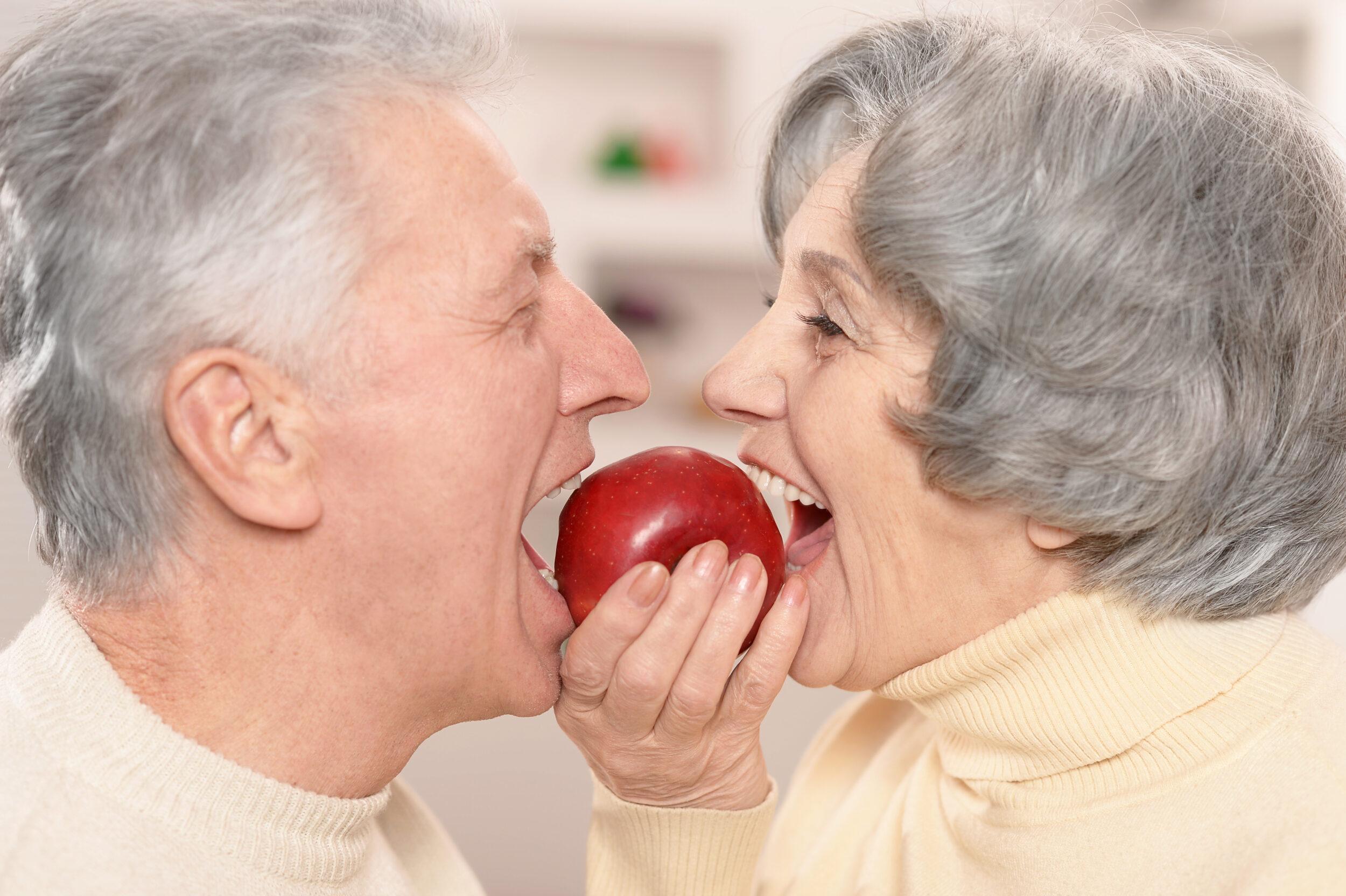 Cute Older Couple Biting Apple Together
