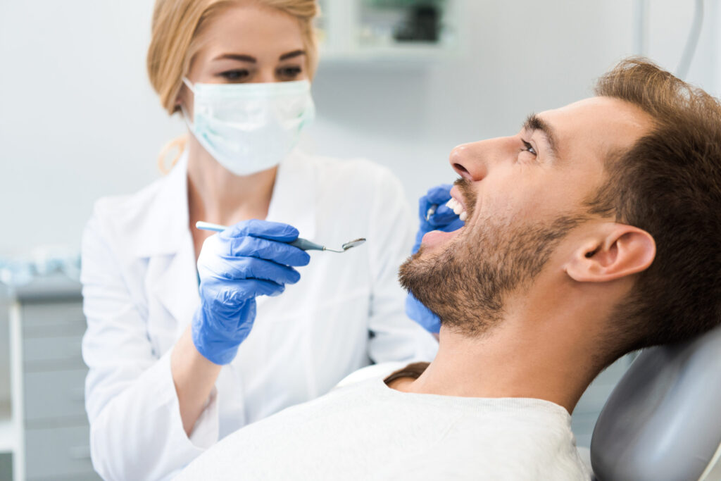 Female Dentist Performing Root Canals On Happy Male Patient