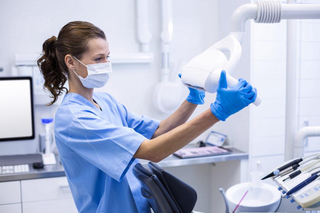 Dental Hygiene Assistant Adjusting Light In Dental Clinic