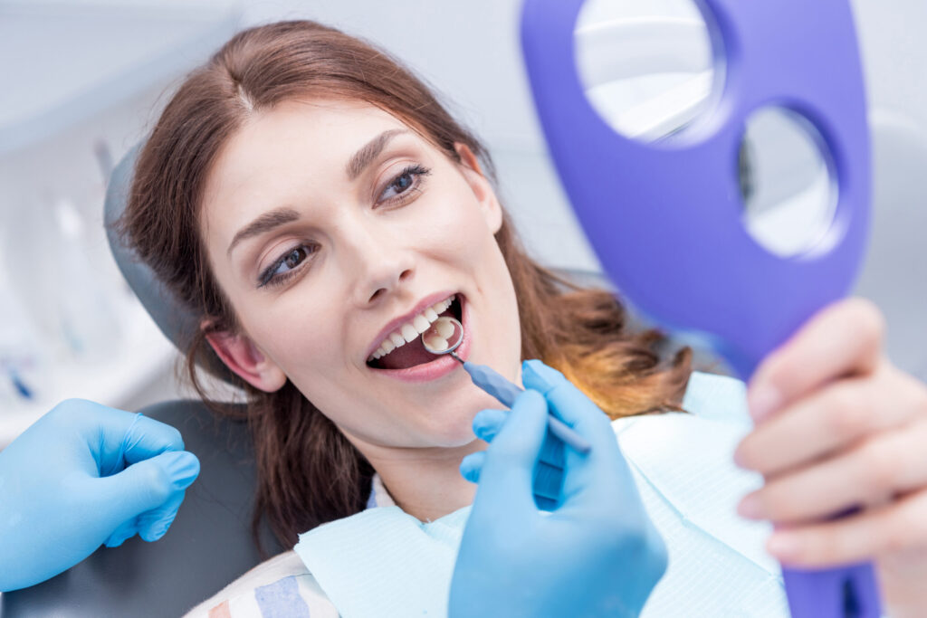 Woman Looking At Teeth With Mirror