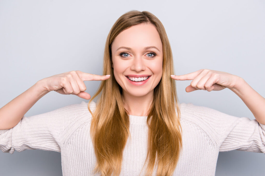 Portrait Of Joyful Satisfied Girl Gesturing Her Beaming White He